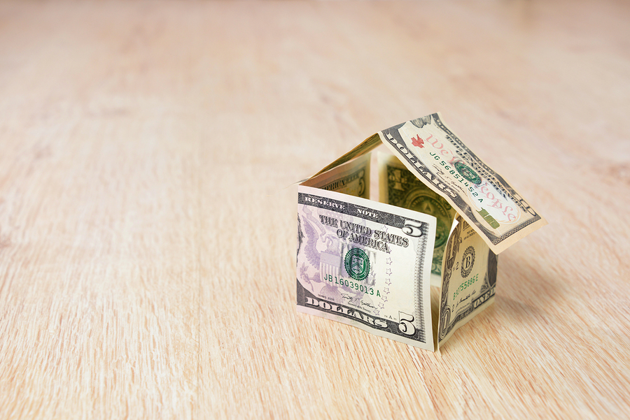 Money house made of dollar bills on wooden background