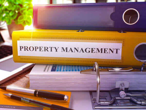 yellow binder holding property management certification course materials
