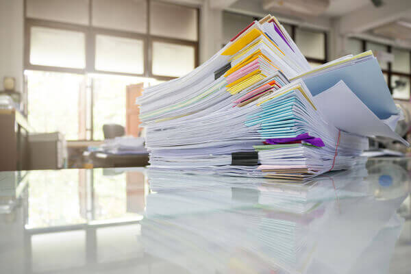 A stack of LLC Paperwork sitting on a white desk